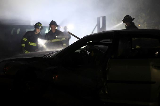Firefighters at night inspecting a car crash