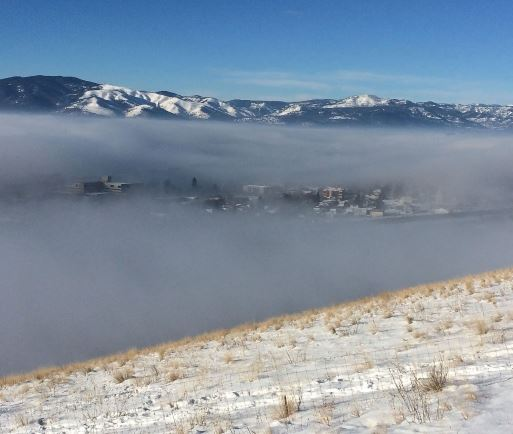 Fog hanging over the Missoula valley with mountains in the distance